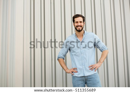 young sexy man with jeans shirt smiling to camera on gray industrial wall