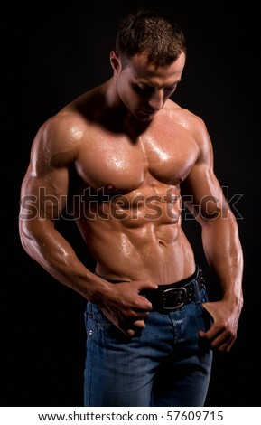 Young sexy man with muscular body on black. - stock photo