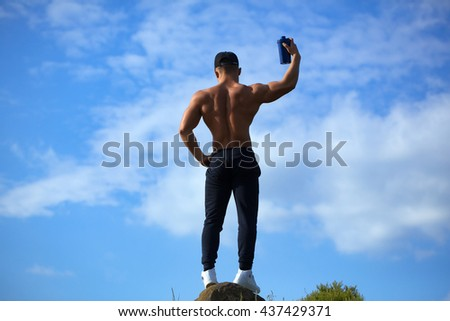 Young sexy man with muscular sexy body and bare torso with chest posing outdoor near sport water bottle on sky natural background