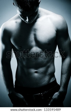 Young sexy muscular man posing - stock photo