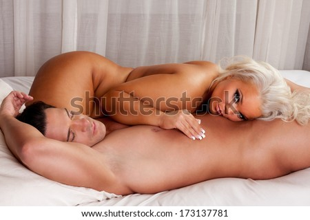 Young sexy naked heterosexual couple in love sleeping in bed - stock photo
