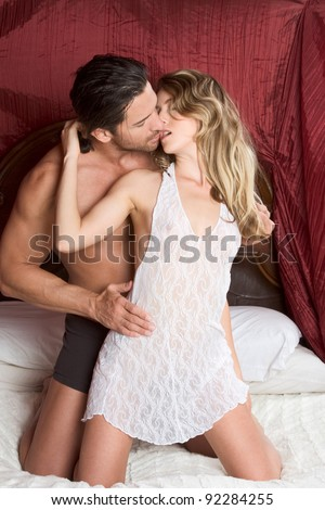 Young sexy naked heterosexual couple making love in bed - stock photo