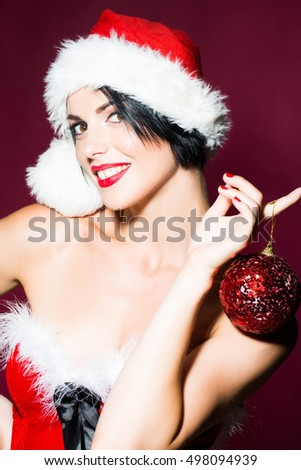 young sexy new year woman or girl with and red lips on pretty smiling happy face in christmas santa claus hat and holiday costume holds decorative ball in studio on purple background