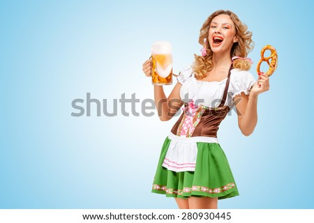 Young sexy Oktoberfest waitress wearing a traditional Bavarian dress dirndl offering a pretzel and beer mug on blue background. - stock photo