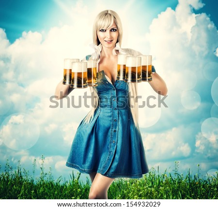 young sexy oktoberfest woman wearing a dirndl holding six beer mugs. outdoor background with grass and sky - stock photo