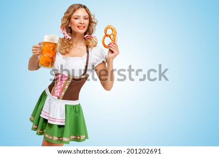Young sexy Oktoberfest woman wearing a traditional Bavarian dress dirndl holding a pretzel and beer mug in hands on blue background.