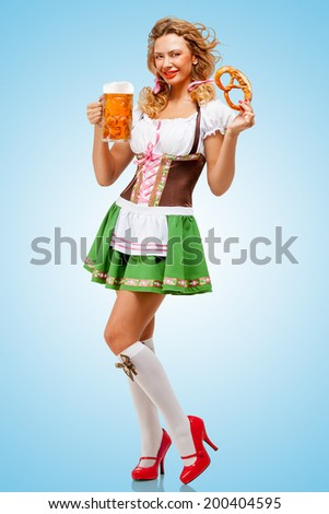Young sexy Oktoberfest woman wearing a traditional Bavarian dress dirndl posing with a pretzel and beer mug in hands on blue background.