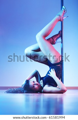 Young sexy pole dance woman. Blue tint.
