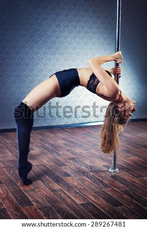 Young sexy pole dance woman in black lingerie. - stock photo