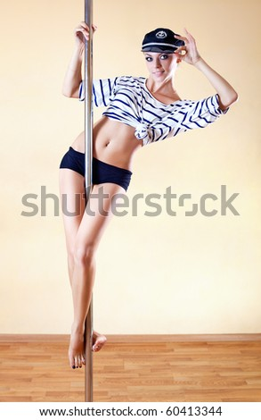 Young sexy pole dance woman in sea captain suit. - stock photo