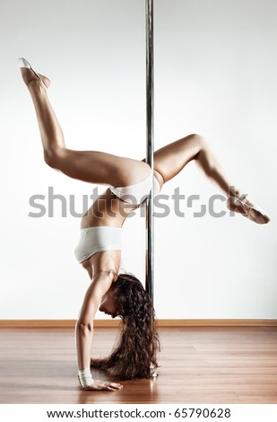 Young sexy pole dance woman. On white wall background. - stock photo