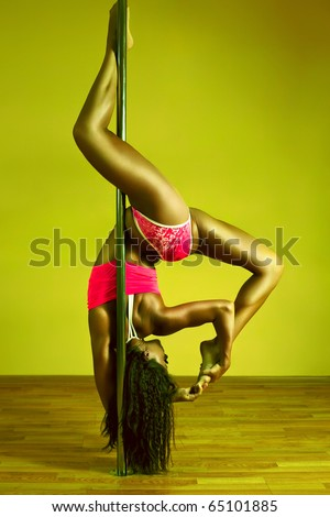 Young sexy pole dance woman. Vibrant yellow and green colors. - stock photo