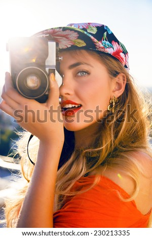 Young sexy sensual blonde woman taking photo on retro vintage hipster camera, smiling and having fun, wearing swag floral bright hat. Lifestyle travel photo of photographer, evening sunlight. - stock photo