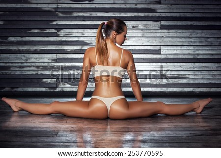 Young sexy slim sports woman in lingerie stretching legs on wall background. - stock photo