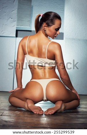 Young sexy slim sports woman in white lingerie sitting on wall background. Backside view. - stock photo