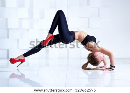 Young sexy slim woman dancer stretching upside down in bright white interior - stock photo