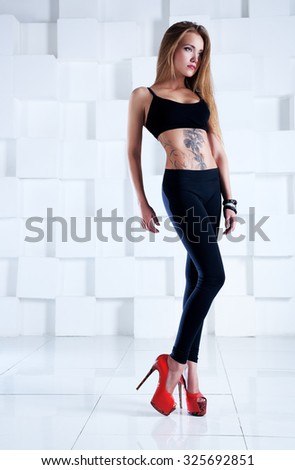 Young sexy slim woman with tattoo on body in black clothing in bright white interior. - stock photo