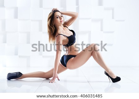 Young sexy sports woman in black lingerie stretching legs on white background - stock photo