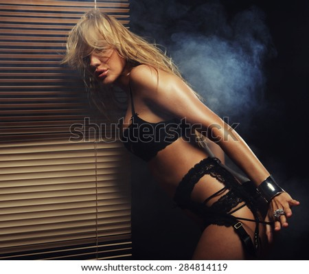 young sexy striptease dancer near Venetian blinds - stock photo