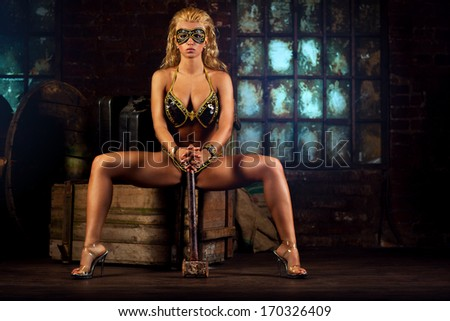 Young sexy strong woman with hammer. - stock photo