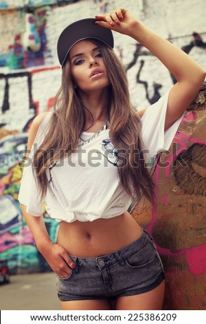 Young sexy swag girl posing in t-shirt and shorts in urban extreme park. Beautiful stylish hipster fashion style portrait - stock photo