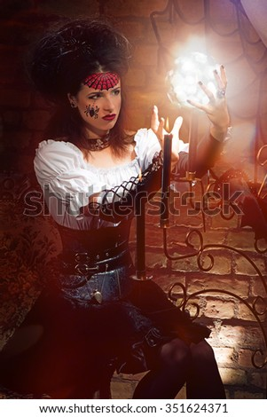 Young sexy witch with candles and magic sphere dressed in vintage dress - stock photo