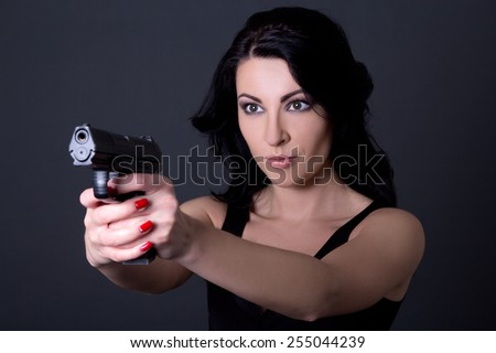 young sexy woman aiming with gun over grey background - stock photo