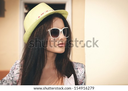 Young sexy woman closeup portrait. Stylish woman posing on the street with interested look and green hat on her head. - stock photo