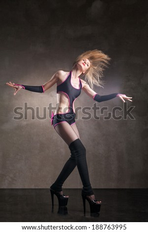 Young sexy woman dancing in studio over gray background