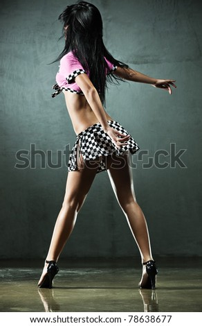 Young sexy woman dancing on wall background. - stock photo