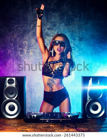 Young sexy woman dj playing music. Big loud speakers, headphones and dj mixer on table.