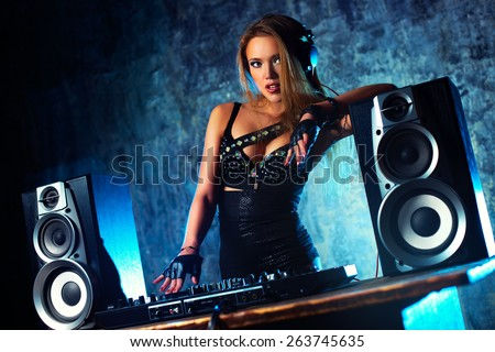 Young sexy woman dj playing music. Big loud speakers, headphones and dj mixer on table. Camera angle view.