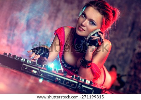 Young sexy woman dj playing music. Headphones and dj mixer on floor. Camera angle view. - stock photo