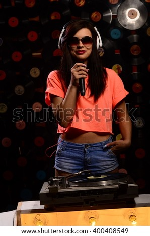 Young sexy woman dj playing music. Headphones and dj mixer on table.