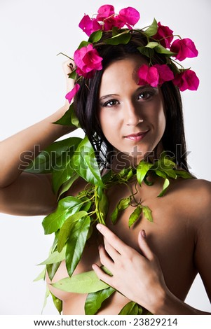 Young sexy woman dressed in flowers and leaves - stock photo