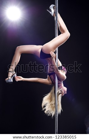 Young sexy woman exercise pole dance against a black background - stock photo