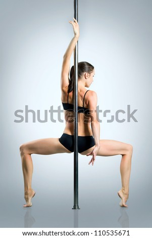 Young sexy woman exercise pole dance against a gray background