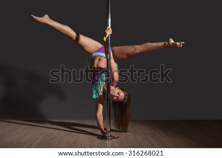 Young sexy woman exercise pole dance before a gray background with floor - stock photo