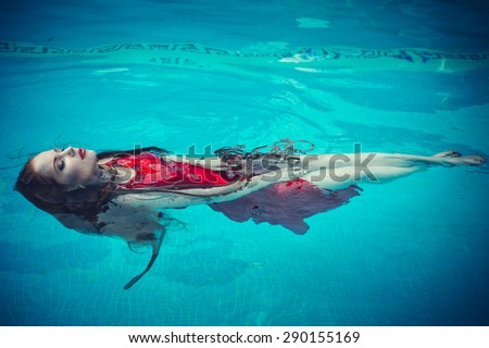 Young sexy woman floating on swimming pool in red dress. Beautiful rich lady who was strangled and thrown off into the water