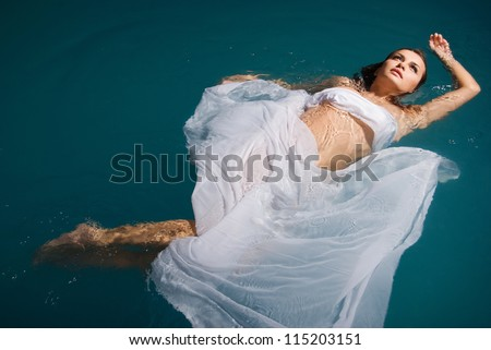 Young sexy woman floating on swimming pool in white dress. beauty shot - stock photo