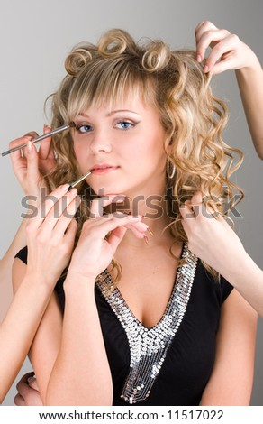 Young sexy woman getting a make-up by many hands - stock photo
