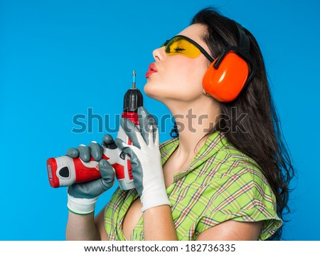 Young sexy woman holding a construction drill - stock photo