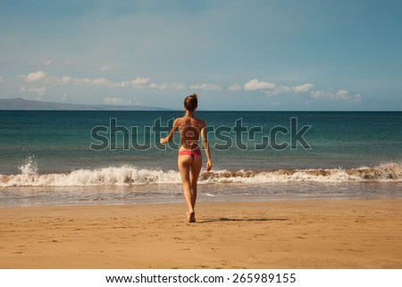 Young sexy woman in a swimsuit walking on the beach, Young Caucasian woman near ocean, Hawaii - stock photo