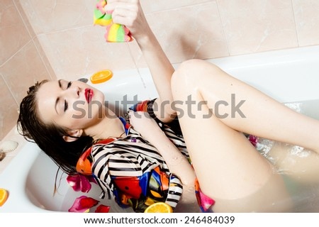 Young sexy woman in bath squeezing shower puff on her leg - stock photo