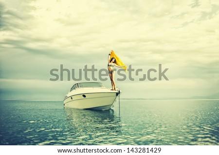 Young sexy woman in bikini enjoying  her private yacht - stock photo