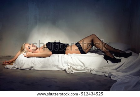 Young sexy woman in black lingerie lying on the bed.