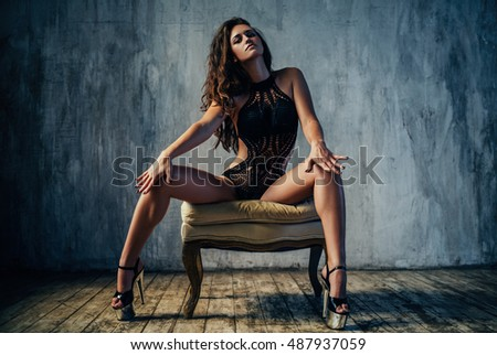 Young sexy woman in black lingerie sitting on chair. Retro style film colors effect.