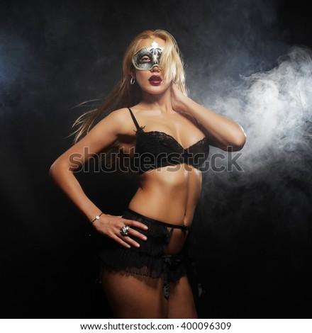 young sexy woman in black lingerie wearing mask - stock photo