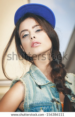 Young sexy woman in blue cap and jeans jacket .  Outdoors, lifestyle. - stock photo