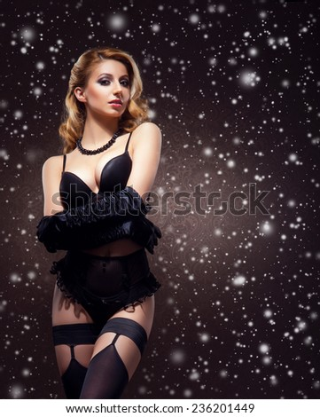 Young sexy woman in erotic lingerie over snowy Christmas background